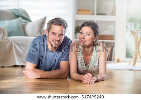 At home, handsome couple in their thirties lying on wooden floor in the living room. the man has gray hair and a beard