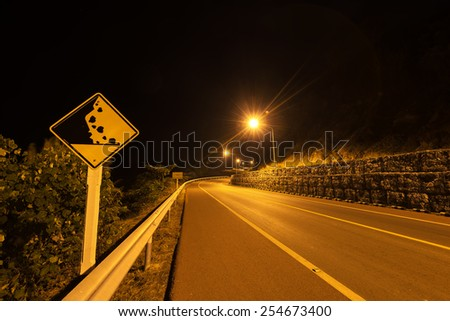 at night Falling Rocks Protection of Winding Road  - stock photo
