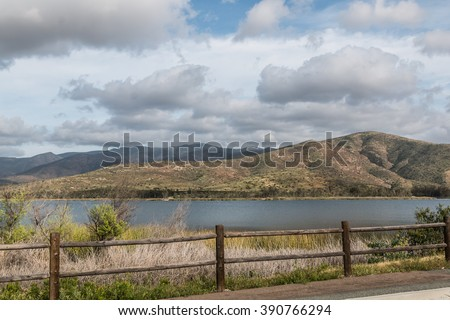 At Otay Lakes County Park in Chula Vista, California, a scenic view of a mountain range, the lake and a fence line.   - stock photo