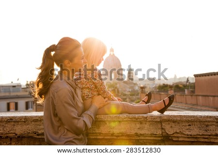 At sunset, a brunette mother in profile is standing behind her blonde daughter, holding her, as she is sitting on a ledge above the city of Rome. In the distance, St. Peter's Basilica. - stock photo