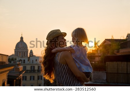 At sunset, with views over Rome, a brunette mother wearing a hat is holding her daughter - seen from behind - in her arms, and talking to her. In the distance, St. Peter's Basilica. - stock photo