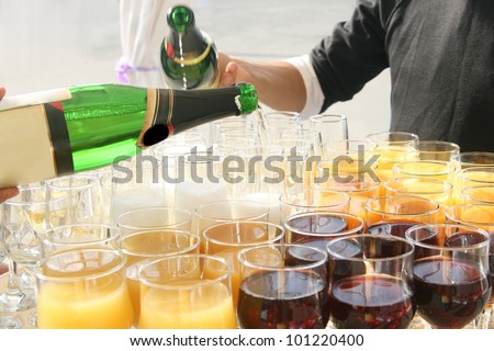 at the banquet table with Fougeres and wine glasses with the juice of red wine and champagne bottles with the hands above the table - stock photo