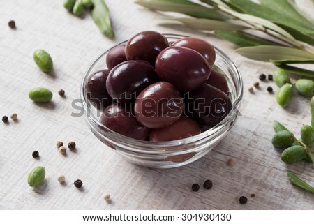 At the center of the frame with black olives bowl framed by branches of the olive tree and scattered peppercorns. Black olives into a bowl. Horizontal shot. Daylight.  - stock photo