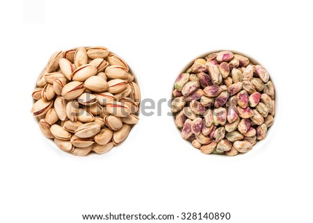 At the center 2 white bowls of pistachios right  of salted roasted pistachios and left of raw pistachio kernels on white background. 2 options prepared for eating pistachios. Horizontal. Top view. - stock photo