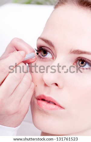 at the cosmetic studio eyeliner on eyes doing make up woman portrait closeup