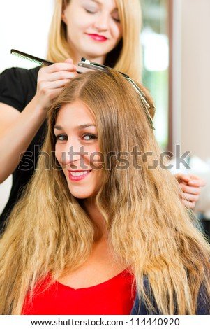 At the hairdresser - woman gets new hair colour or highlights - stock photo