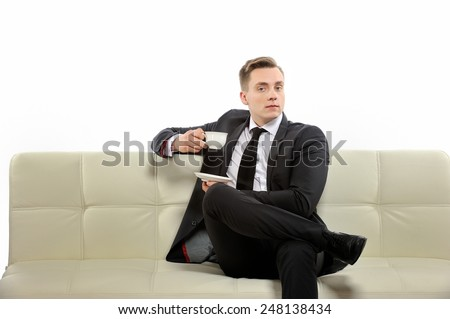 At the moment is break time for me, but I will listen to you. Young businessman with a cup of coffee sitting on the couch, drinking coffee.