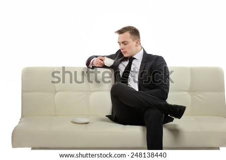 At the moment is break time for me. Young businessman with a cup of coffee sitting on the couch, drinking coffee.
