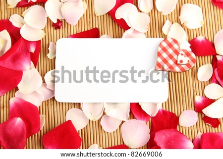 At the rose petals is white piece of paper and a red heart. Postcard - stock photo