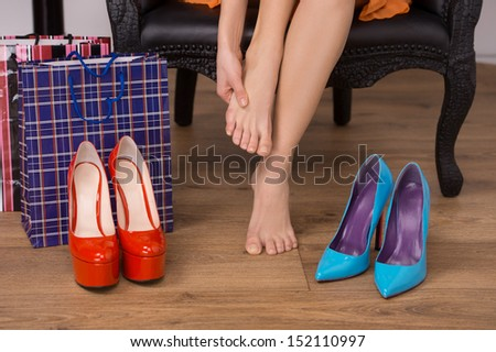 At the shoe store. Close-up of woman sitting at the chair and touching her foot while shoes lying on the floor