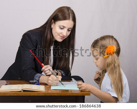 At the table sat a teacher and a student. Student teaches lessons, the teacher helps. - stock photo