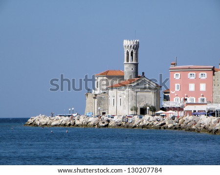 At the tip of the peninsula in Piran is the Church of St. Clement and a lighthouse, The Church is also known as the Church of Our Lady of Health because of it's role during a 17th century plague. - stock photo