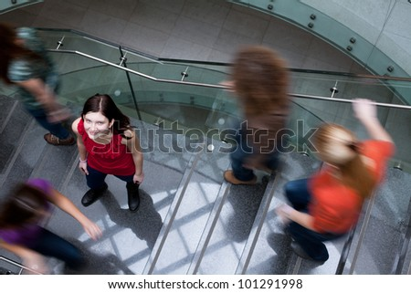 At the university/college - Students rushing up and down a busy stairway - confident pretty young female student looking upwards (color toned image) - stock photo
