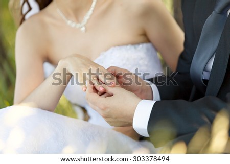 At the wedding, the groom puts the ring on the bride's finger. Hand of the groom and the bride with wedding rings at a wedding party . Outdoors - stock photo