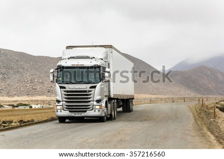 ATACAMA, CHILE - NOVEMBER 14, 2015: Semi-trailer truck Scania R400 at the gravel interurban freeway through the Atacama desert. - stock photo