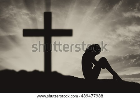 Atheism. Atheist woman sits with his back to the cross
