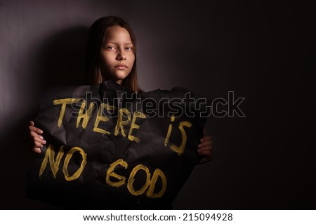 "Atheist teen girl holding a banner with the inscription-""THERE IS NO GOD"""