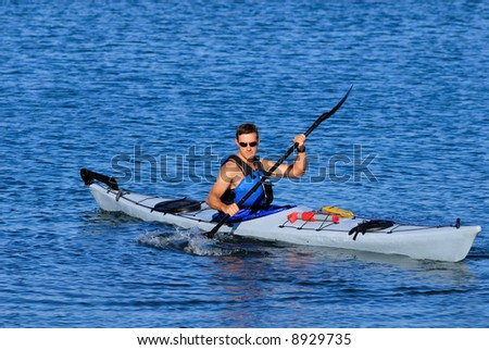 Atheltic man is kayaking in cal blue waters of Mission Bay, San Diego, Califronia. Copy space on top.