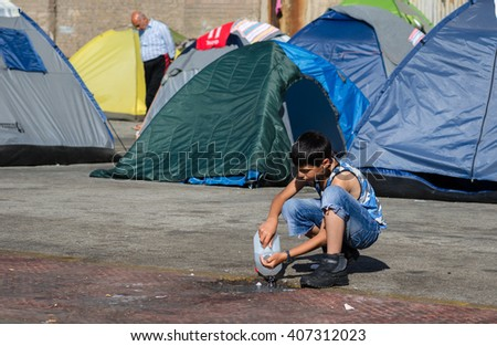 Athens – APRIL 17:  Syrian refugee drink water from the canister  in a camp for refugees from Syria  April 17, 2016 in Athens.