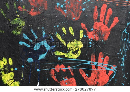 ATHENS, GREECE - APRIL 27, 2015: Messy handprints and dripping paint on textured wall background. Colorful hand imprints abstract graffiti pattern.