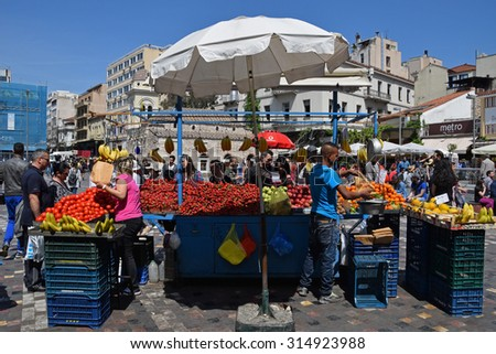 ATHENS, GREECE - APRIL 27, 2015: People buying fruit and vegetables from outdoors grocery store kiosk at Monastiraki square.