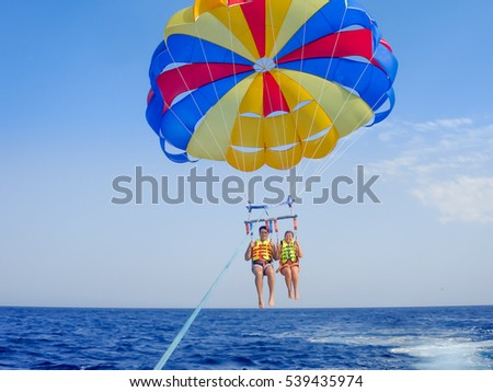 Athens, Greece - august 28, 2011: Parasailing in a blue sky in Santorini beach. Parasailing is a popular recreational activity there. This is one of the most beautiful Islands on the planet.