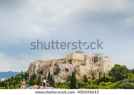 ATHENS, GREECE - 21 AUGUST 15 : People at rock near Acropolis from far, Athens, Greece in a cloudy day of summer
