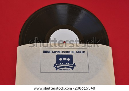 ATHENS, GREECE - AUGUST 1, 2014: Vinyl record inner sleeve with 1980s anti copyright infringement campaign skull and crossbones with cassette tape head. Home taping music piracy. - stock photo