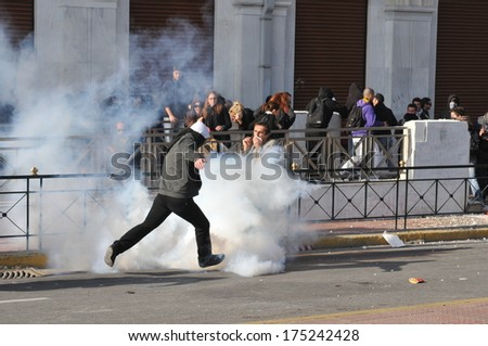 ATHENS, GREECE- DEC. 12. Protester trying to avoid tear gas canister. during demonstration, in the centre of Athens,, in Athens, December 10, 2008. - stock photo