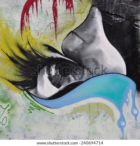 ATHENS, GREECE - DECEMBER 10, 2014: Female eye with big eyelashes and river of tears colorful graffiti on city wall. Urban street art. - stock photo