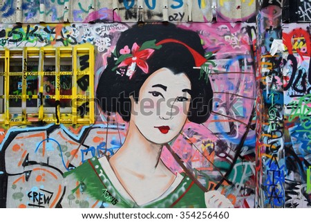 ATHENS, GREECE - DECEMBER 10, 2015: Geisha graffiti traditional japanese female figure with parasol on colorful spray painted wall. Urban street art. - stock photo