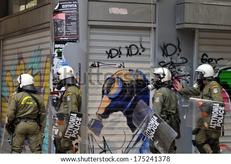 ATHENS, GREECE - DECEMBER 07. Riot police officers wearing a gas mask in front of graffiti of a gas mask, during clashes in Athens, December 07, 2008.  - stock photo
