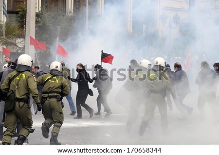 ATHENS, GREECE-FEB.23.  Protesters holding flags being chased by riot police during demonstration in Athens, February 23, 2011. - stock photo