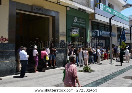 ATHENS, GREECE - JULY 1, 2015: Long queue of people waiting for money at ATM cashpoint. Banks are closed and capital controls allow cash withdrawal of 60 euro per day. Greek financial crisis.