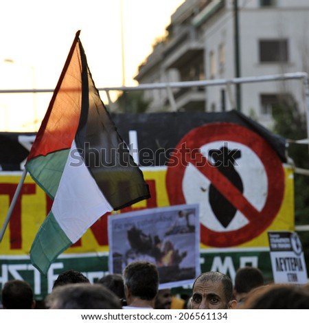 "Athens, Greece, July 22, 2014: Palestinian flag and sign ""stop bombs"" among the march of solidarity with the Palestinian people and free Gaza. The demonstration was against civilian deaths from bombs. - stock photo"