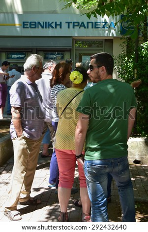 ATHENS, GREECE - JULY 1, 2015: People queuing at bank branch to withdraw cash money from ATM machine cashpoint. Banks are closed and capital controls are implemented as Greece heads for a referendum. - stock photo