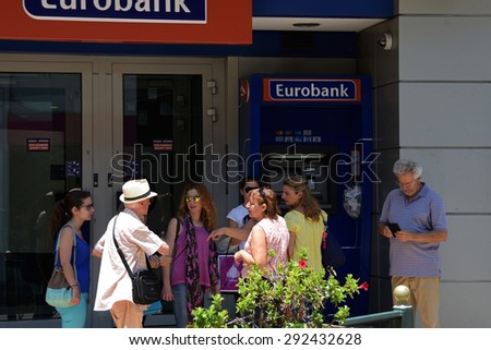 ATHENS, GREECE - JULY 1, 2015: People waiting at atm machine queue at greek bank inform a tourist that there are no capital controls on credit cards issued abroad and no daily cash limit for visitors.