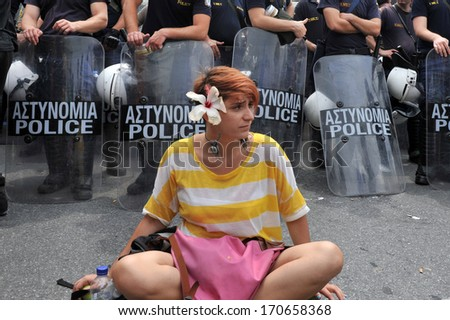 ATHENS-GREECE,JUNE 15. A young girl is protesting peacefully in front of a riot police during demonstration in Athens, June 15, 2011.  - stock photo