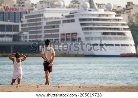 Athens, Greece - June 29: Unidentified people watching a cruise ship departing from Piraeus, a port in Athens, Greece on June 29, 2014. - stock photo