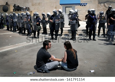 ATHENS, GREECE - MAY 20: A young couple of anti-cuts protesters, sits peacefully opposite the riot police officers in front of Greek Parliament ,in Athens, May 20, 2010. - stock photo