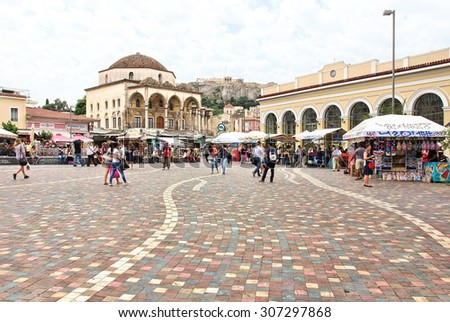 ATHENS, GREECE - MAY 19, 2015: Financial crisis in Greece. Athenians and tourists in Monastiraki Square, with market stalls, underground station, Tzistarakis Mosque and the Acropolis in the background