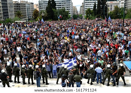 ATHENS, GREECE -MAY, 05: Protesters, with Greek flags, demonstrate against government austerity measures, outside the Greek Parliament in Syntagma Square Athens, May 05, 2010.  - stock photo