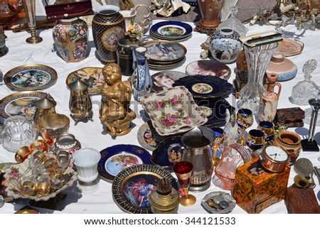 ATHENS, GREECE - MAY 31, 2015: Vintage glass decorative objects antique porcelain plates and vases for sale at flea market.