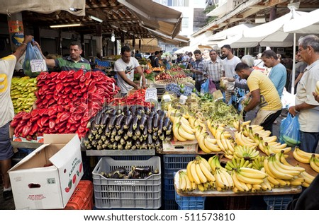ATHENS, GREECE - OCTOBER 01, 2016: People buying fruit and vegetables from outdoors grocery store kiosk at Monastiraki square
