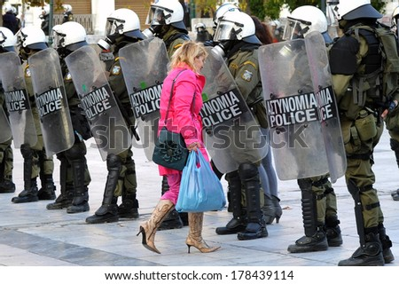 ATHENS, NOV. 17. Greek economic crisis. During a day with a demonstration, a woman carrying shopping bags goes through the riot police line in Athens, Syntagma  square, November 17, 2014 - stock photo