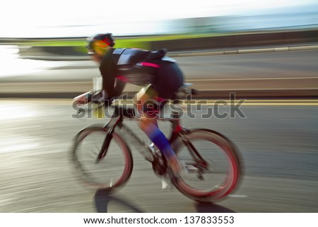 Athlet riding bicycle at sunny day on coastal road, blurred motion