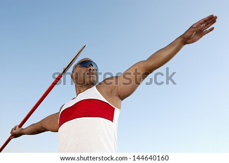 Athlete about to throw javelin half length - stock photo