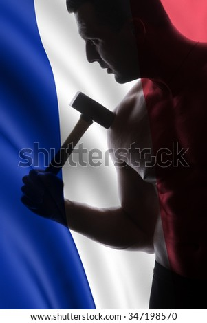 athlete and hammer on French flag background  - a very beautiful young guy with a nice muscle fitness and bodybuilder coach hold in strong arms and big metal hammer - stock photo