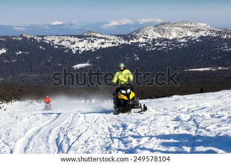 Athlete ascends the mountain on a snowmobile. Southern Urals, Russia. - stock photo