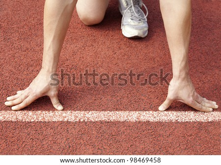 athlete at the start line of the stadium - stock photo